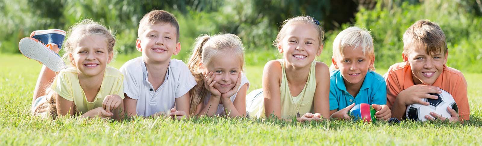 Gruppe von Kindern liegen im Gras