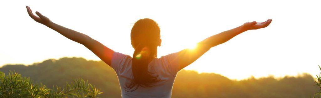 glückliche Frau streckt die Arme in den Himmel