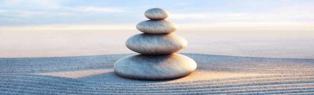 Steine im Sand harmonisch angeordnet